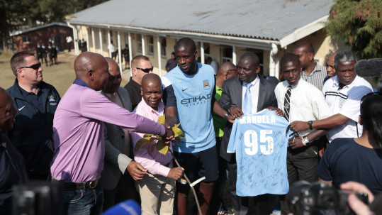 Manchester City's Yaya Toure plants a tree as he visits a school built on the site where Nelson Mandela cast his first vote